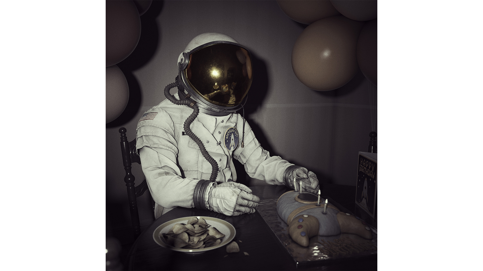 Full render of Transmissions, a CG hyper realistic scene of a spaceman seated at a table with a rocket birthday cake, a bowl of crisps and balloons. The render is photographic with a vintage, 1970s saturation to the colour