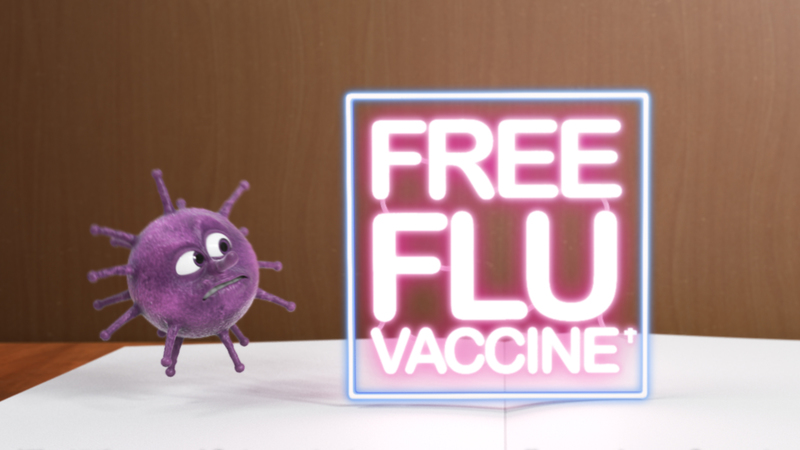 Close up of Vince the virus reacting to a neon sign that states 'Free Flu Vaccine'