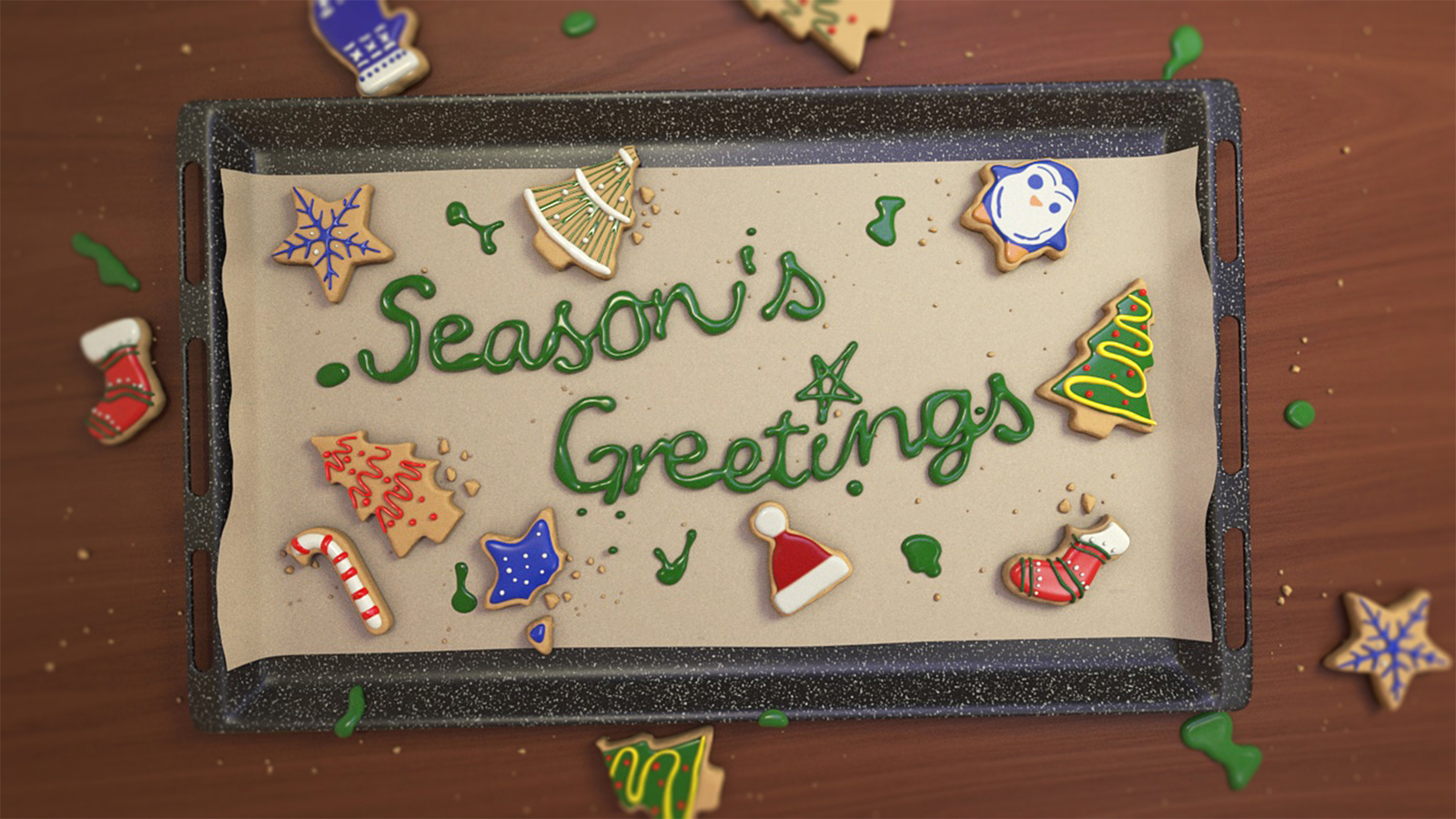Colour still of baking tray from animation with biscuits iced, drops of icing around the tray and the lettering 'seasons greetings' on baking parchment, surrounded by the biscuits on the tray
